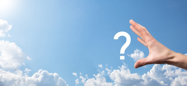 Male hand holding question mark icon on blue background.banner with copy space. place for text.