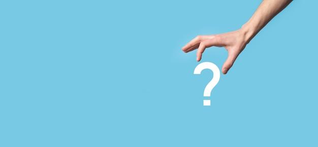 Мужская рука, держащая значок вопросительного знака на синей поверхности