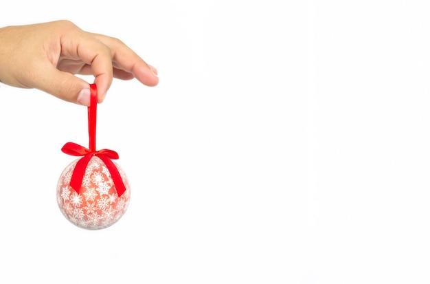 白い背景で隔離赤いクリスマスボールを持っている男性の手。