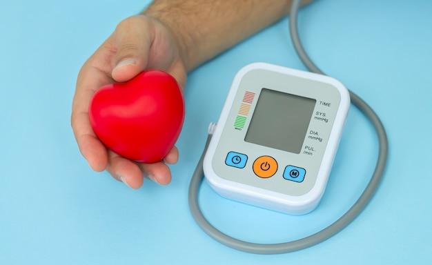 血圧を測定するための電子眼圧計の横に赤いハートを持っている男性の手