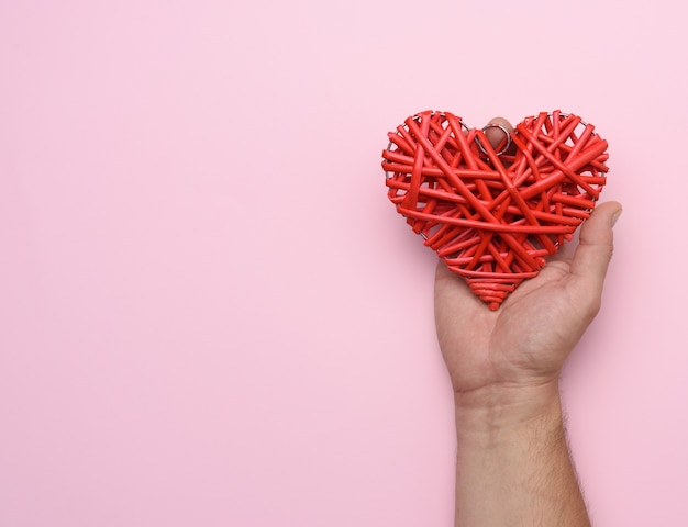 Male hand holding a red wicker heart on pink, love concept