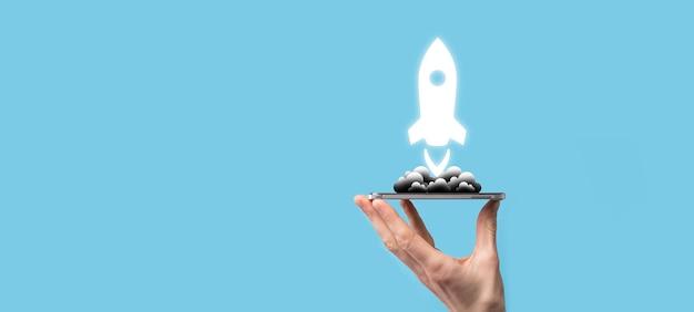 Мужская рука, держащая значок ракеты, которая взлетает, запускается на синем фоне. ракета запускается и вылетает, запуск бизнеса, маркетинг иконок на современном виртуальном интерфейсе. концепция запуска.