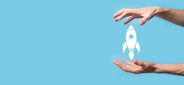 Мужская рука, держащая значок ракеты, которая взлетает, запускается на синем фоне. ракета запускается и улетает, запуск бизнеса, маркетинг иконок на современном виртуальном интерфейсе. концепция запуска.