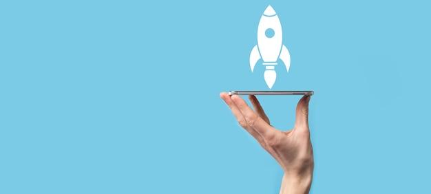 離陸するロケットアイコンを持っている男性の手は、青い背景で起動します。ロケットが打ち上げられて飛び出し、ビジネスが始まり、最新の仮想インターフェイスでアイコンマーケティングが行われます。