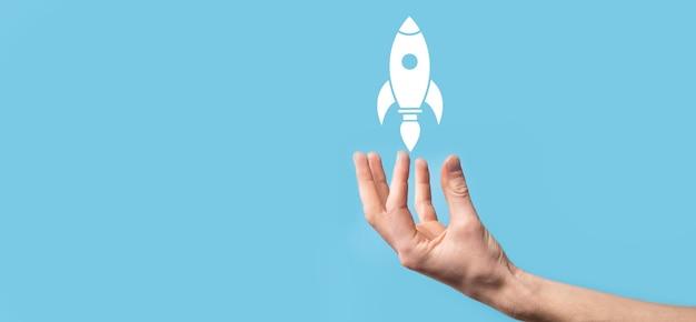 離陸するロケットアイコンを持っている男性の手は、青い背景で起動します。ロケットが打ち上げられて飛び出し、ビジネスが始まり、最新の仮想インターフェイスでアイコンマーケティングが行われます。スタートアップのコンセプト。