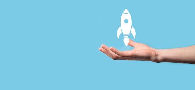Мужская рука, держащая значок ракеты, которая взлетает, запускается на синем фоне.