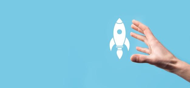 Мужская рука держит значок ракеты, которая взлетает, запускается на синей поверхности