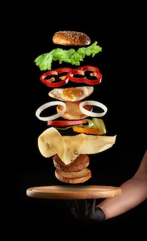 Male hand holding a round wooden board and floating layers of cheeseburger with chicken egg and meat cutlet on black background, fast food