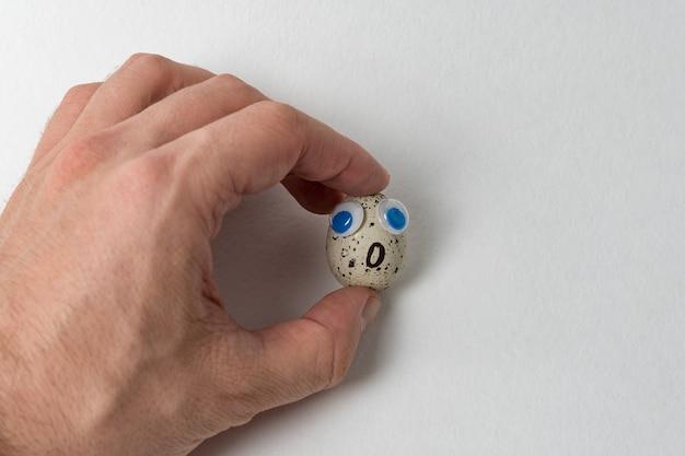 Мужская рука, держащая распиленное яйцо с большими глазами. яйцо с забавным лицом на белом фоне.