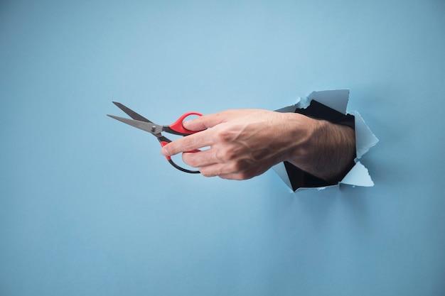 Male hand holding scissors on blue scene