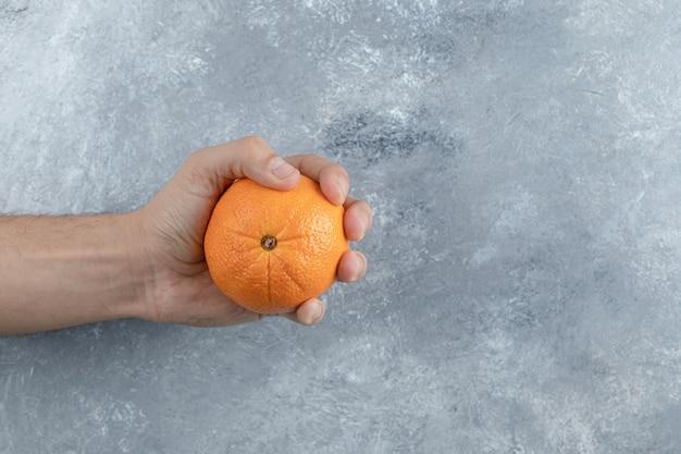 Mano maschio che tiene singola arancia sul tavolo di marmo.