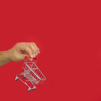 赤い背景に小さなショッピングカートのトロリーを持っている男性の手。オンラインショッピングと短納期のコンセプト。