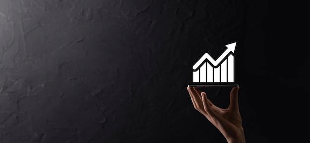 Мужской рукой, держащей смарт-мобильный телефон со значком графика. проверка анализа графика роста данных продаж и фондового рынка в глобальной сети. бизнес-стратегия, планирование и цифровой маркетинг