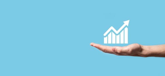 Мужская рука, держащая смарт-мобильный телефон со значком графика. проверка анализа графика роста данных продаж и фондового рынка в глобальной сети. бизнес-стратегия, планирование и цифровой маркетинг.