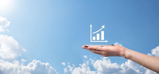 그래프 아이콘이 있는 스마트 휴대폰을 들고 있는 남성 손. 글로벌 네트워킹에서 판매 데이터 성장 그래프 차트와 주식 시장을 분석하는 검사. 비즈니스 전략, 계획 및 디지털 마케팅.
