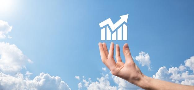 그래프 아이콘이 있는 스마트 휴대폰을 들고 있는 남성 손. 글로벌 네트워킹에서 판매 데이터 성장 그래프 차트와 주식 시장을 분석하는 검사. 비즈니스 전략, 기획 및 디지털 마케팅