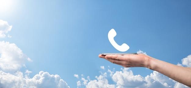 Мужской рукой, держащей смарт-мобильный телефон с значок телефона. позвоните сейчас бизнес-коммуникационный центр поддержки клиентов концепции технологии обслуживания.