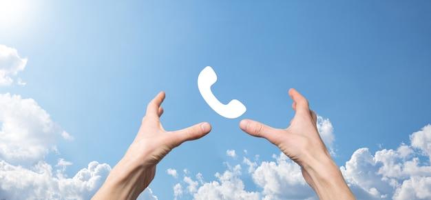 電話アイコン付きのスマート携帯電話を持っている男性の手。今すぐお電話くださいビジネスコミュニケーションサポートセンターカスタマーサービス技術コンセプト。