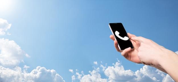 전화 아이콘이 있는 스마트 휴대전화를 들고 있는 남성의 손입니다. 지금 비즈니스 커뮤니케이션 지원 센터 고객 서비스 기술 개념에 전화하세요.