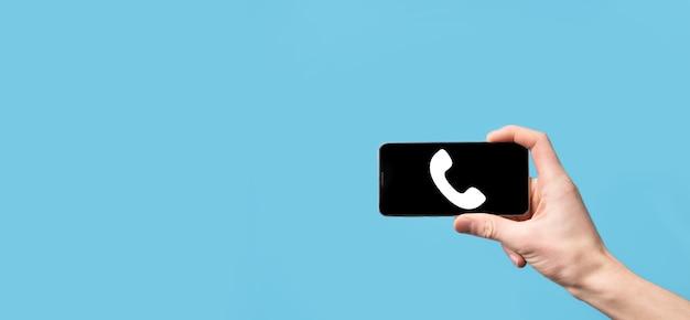 Мужская рука, держащая смарт-мобильный телефон со значком телефона