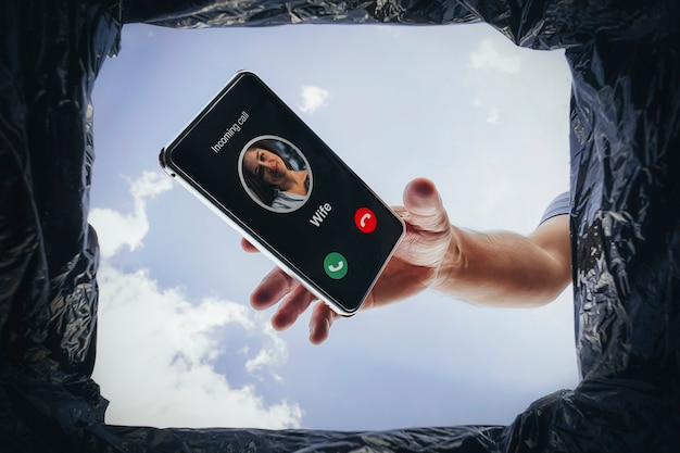 Male hand holding smart phone with incoming call from wife and throwing the phone in the trash can. call from an annoying wife. divorce of the marriage. concept - problem is in relationship.