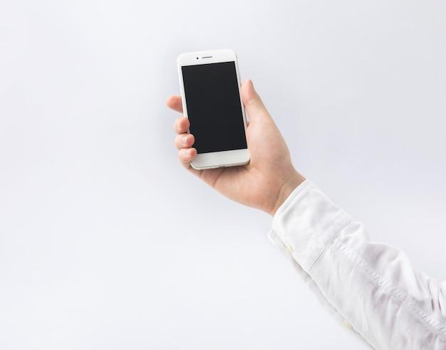 スマートフォン、白い背景の上の携帯電話を持っている男性の手。