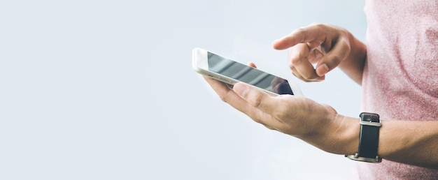 スマートフォン、バナーサイズの背景にコピースペースを持つ携帯電話を持っている男性の手。