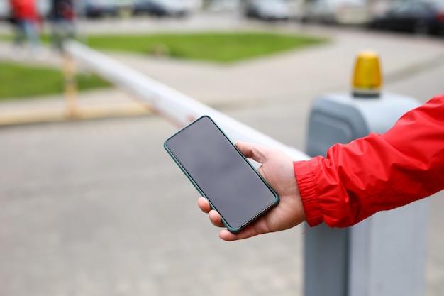 Мужской рукой, держащей смартфон переключения предельной планки во дворе проход крупным планом