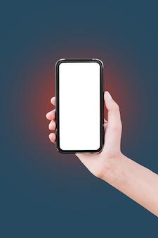 赤の薄暗い光で濃い青の背景にモックアップのための空白の画面でスマートフォンを持っている男性の手