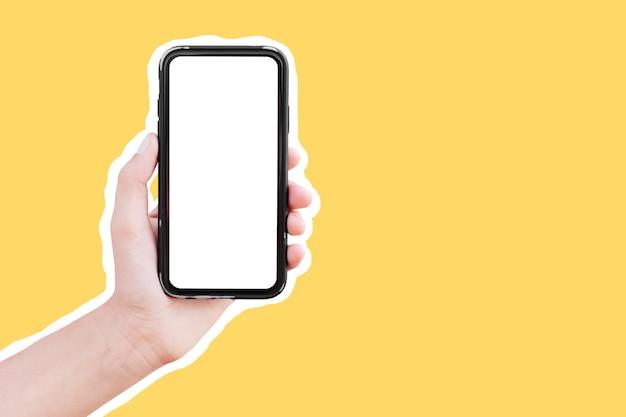 黄色の背景で隔離の空白の画面でスマートフォンを持っている男性の手