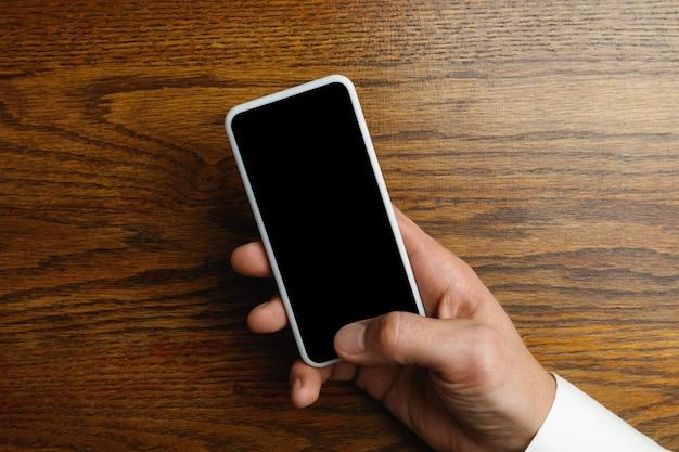 テキストやデザインの木製の壁に空の画面でスマートフォンを持っている男性の手。連絡先またはビジネスで使用するための空白のガジェットテンプレート。財務、オフィス、購入。コピースペース。