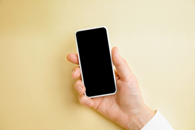 Male hand holding smartphone with empty screen on yellow wall for text or design. blank gadget templates for contact or use in business. finance, office, purchases.  copyspace.