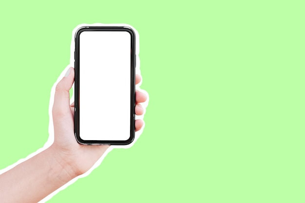 Male hand holding smartphone with mockup, isolated with white contour on green.