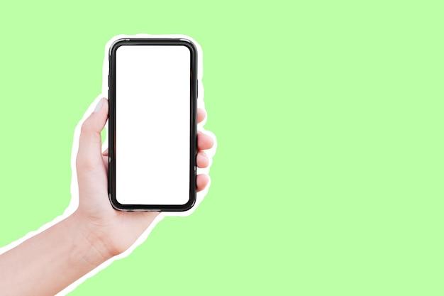 緑の白い輪郭で隔離のモックアップとスマートフォンを持っている男性の手。