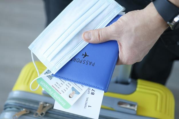 スーツケースと予防接種パスポート付き保護マスクを持っている男性の手。 covid19パンデミックコンセプト中の旅行