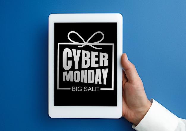 青い背景にサイバーマンデーの言葉でタブレットを持っている男性の手。テクノロジー、モダン、ガジェット、ビジネス、広告。ブラックフライデー、サイバーマンデー、販売、金融、お金のオンライン購入の概念。