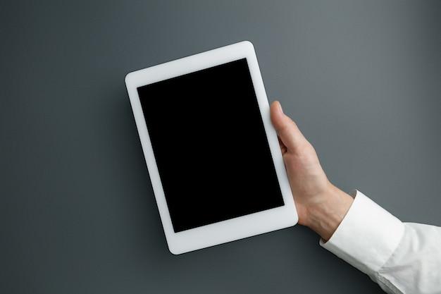 Мужская рука держит планшет с пустым экраном на сером