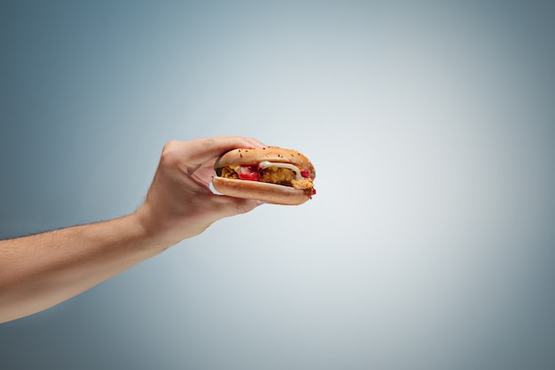 Male hand holding tasty hamburger