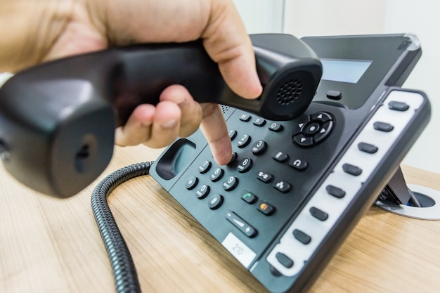 Male hand holding telephone receiver while dialing a telephone number to make a call