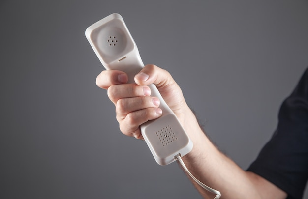 Male hand holding telephone receiver.