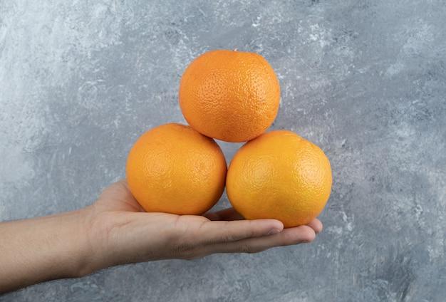 Mano maschio che tiene tre arance sul tavolo di marmo.
