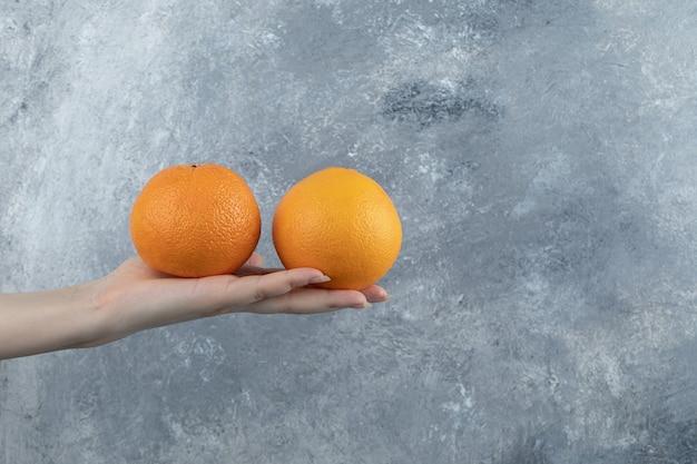 대리석 테이블에 오렌지 두 개를 들고 있는 남성 손.