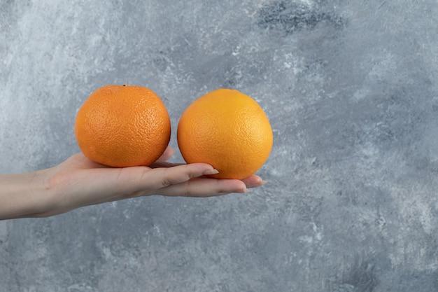 Мужская рука держит два апельсина на мраморном столе.