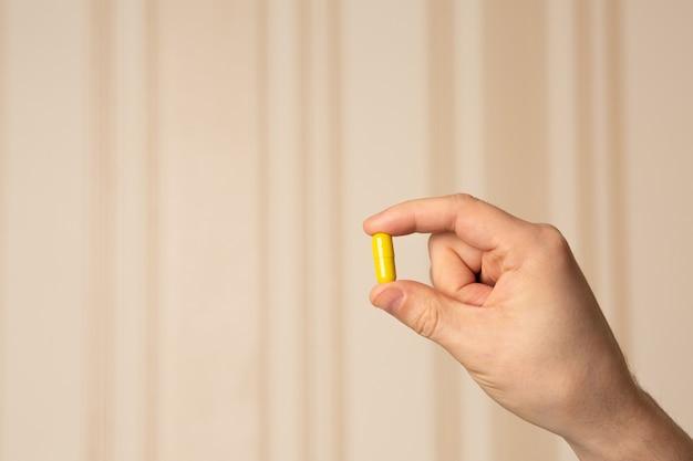 베이지색 줄무늬 배경에 비타민 c 캡슐을 들고 있는 남성 손. 텍스트를 위한 공간