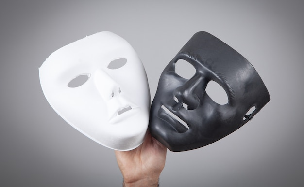 Male hand holding white and black mask. fake, anonymous