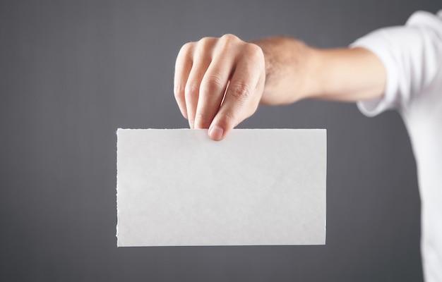 白い白紙を持っている男性の手。
