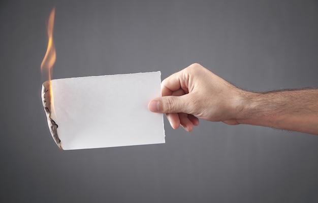白い焦げた紙を持っている男性の手。