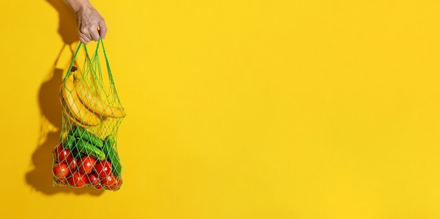Male hand holding a white mesh bag with vegetables on yellow background with copy space. zero waste shopping concept.