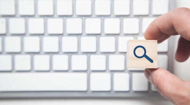 コンピューターのキーボードで木製の空白の立方体を持っている男性の手。
