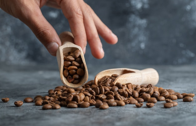 Male hand holding wooden spoon of aromatic coffee beans on marble background